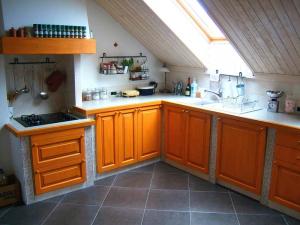 Zidovi kuhinje so oblečeni v ploščice, kar je lažje za vzdrževanje kuhinje.