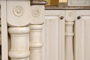 Masivni leseni stebrički z ornamenti kot detajl kuhinje